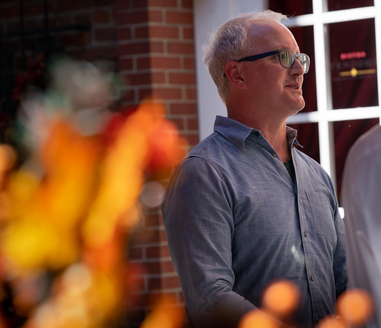Vinmarket – man with glasses behind leaves